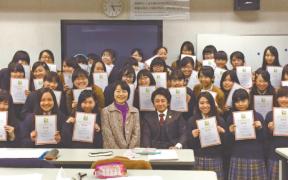 校長の漆氏と垣内氏を囲む、UM認定証を手にした生徒たち。