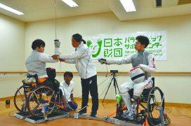 車いすフェンシングの加納慎太郎選手(右)と、笹島貴明選手(左)。真ん中で説明する小松理事長